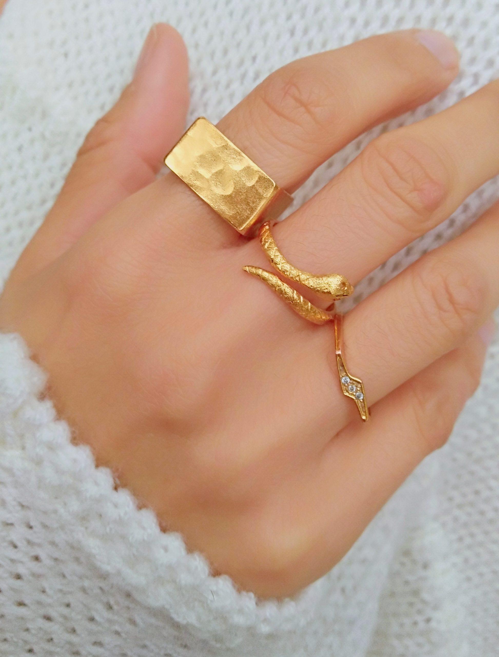 Mano de modelo usando tres anillos: cuadrado, serpiente y rayo con diamantes